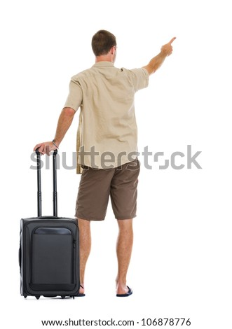 Tourist with wheels bag pointing on copy space. Rear view - stock photo