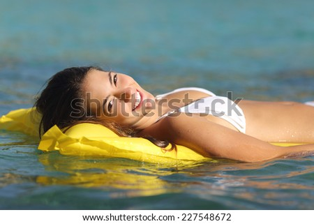 Tourist woman bathing in a tropical sea floating on an inflatable bed and enjoying summer holidays - stock photo