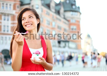 Tourist woman eating ice cream in Quebec City in front of chateau frontenac in Quebec City, Quebec, Canada. - stock photo
