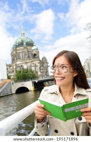 Tourist woman on boat tour Berlin, Germany having fun smiling happy while enjoying mini cruise reading guidebook. Europe travel vacation holiday concept. Multiracial Asian Caucasian woman. - stock photo