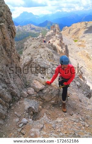 Tourist woman walking a rocky trail, Dolomite Alps, Italy - stock photo