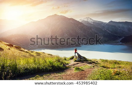 Tourist woman with hat enjoying beautiful sunrise on the lake in the mountain