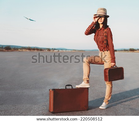 Tourist woman with vintage suitcase looking through binoculars on road, airplane in sky