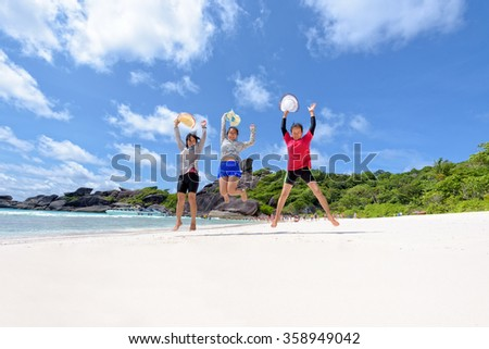 Tourist women three generation family jumping for happy on beach near the sea under sky and clouds of summer at Koh Similan Island in Mu Ko Similan National Park, Phang Nga province, Thailand - stock photo