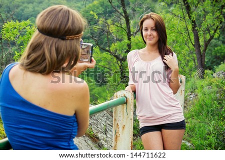 Tourist / Young woman take a photo from her beautiful girlfriend