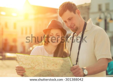Touristic couple looking at map on the city street under sunlight.