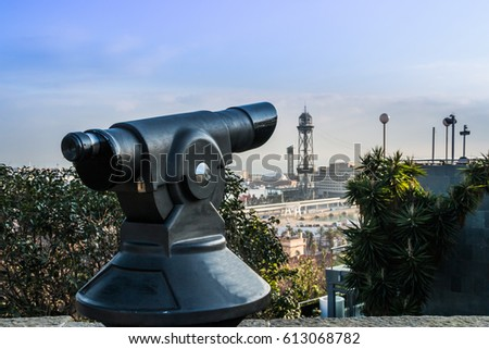 Touristic telescope and blurred city on background. Old metal binoculars on background viewpoint. Barcelona, Spain.