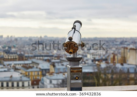 Touristic telescope overlooking Montmartre hill with scenic city view in Paris, France - stock photo