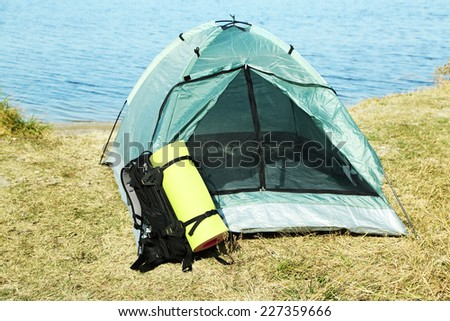 Touristic tent on dried grass near the sea - stock photo