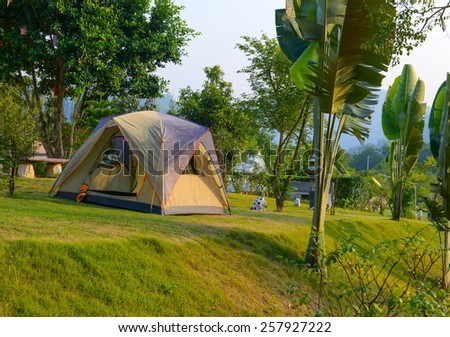 Touristic tent on green grass in a forest resort surrounded by mountains and beautiful gardens at Suanpeung, Ratchaburi, Thailand.