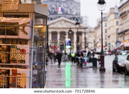 Touristic view at the city: Paris near the Pantheon with souvenir shop, blurred Pantheon, street, buildings, cars and walking people. November 3, 2014.