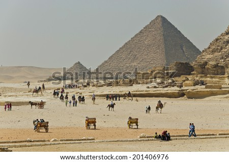 Tourists and natives are near ancient Egyptian pyramids. The Giza Necropolis has been a popular tourist destination since antiquity. - stock photo