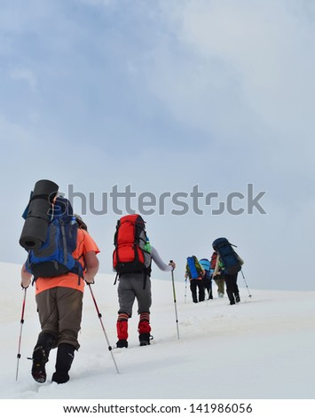 Tourists are in winter in mountains - stock photo
