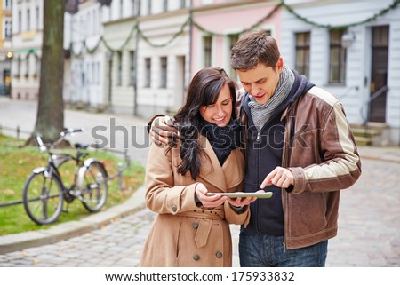 Tourists couple in a city navigating with a tablet computer - stock photo