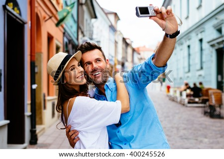 tourists couple taking selfie on city street - stock photo
