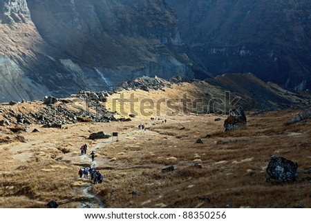 Tourists descend on the path to the Machhepuchare Base Camp - Nepal, Himalayas - stock photo