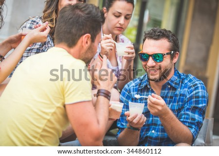 Tourists eating slush, talking and looking each other - stock photo