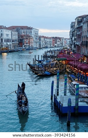 Tourists enjoying the view from gondola glided by a gondolier on grand canal at dusk in Venice Italy ~ Beautiful scenery of Venice at blue hour, from Rialto Bridge(vertical framing & nostalgic effect) - stock photo