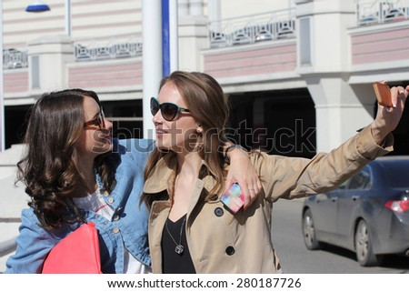 Tourists, girlfriends taking photo with mobile phone in city - stock photo