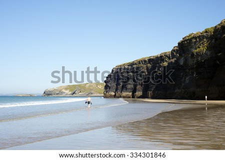 tourists in ballybunion beach and cliffs on the wild atlantic way at low tide - stock photo