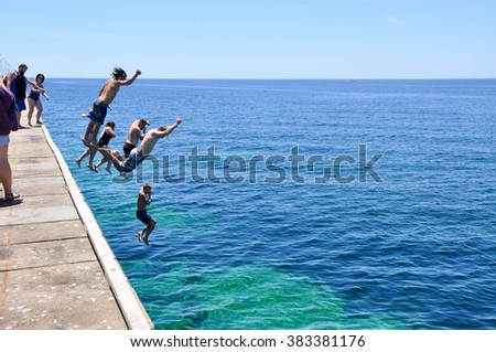 Tourists jumping off the Busselton Jetty in Western Australia/Jetty Leap/BUSSELTON,WA,AUSTRALIA-JANUARY 15,2016:Tourists leaping off Busselton Jetty into Indian Ocean in Busselton, Western Australia.  - stock photo