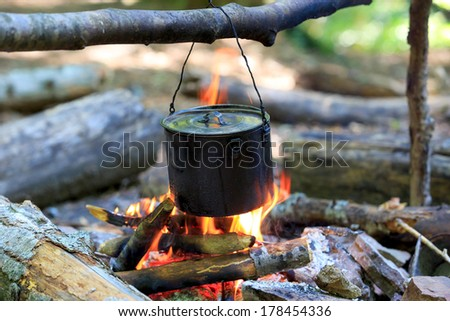 tourists kettle on campfire - stock photo