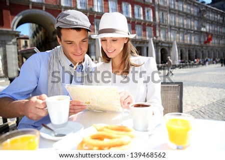 Tourists looking at city map in Spanish restaurant - stock photo