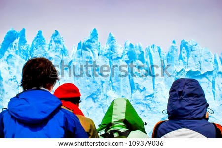 Tourists looking at gigantic icebergs from a ship - stock photo