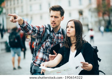 Tourists looking for landmarks in city using map - stock photo