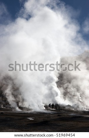 Tourists near erupting geyser, Chile - stock photo