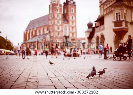 Tourists on market square against blurred St. Mary's Basilica in Krakow, Poland - stock photo