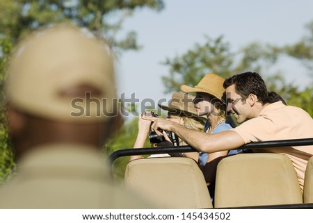 Tourists on safari pointing at view with blurred guide in foreground - stock photo