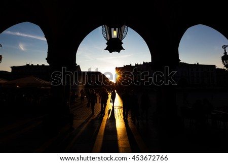 Tourists on the main market square in Cracow. View at sunset from the Cloth Hall, Polish Sukiennice. - stock photo