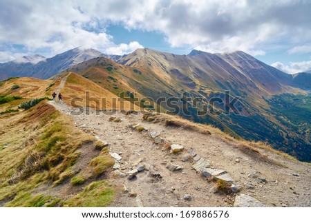 Tourists on trail from Trzydniowianski Wierch (1758 m) to Konczysty Wierch (2002 m) High mountains in Europe. Tatras, Poland. Nature preserve.  - stock photo
