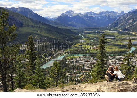 Tourists photograph a panorama of a town Banff in a Bow river valley from top of mountain (Banff National Park. Alberta. Canada)