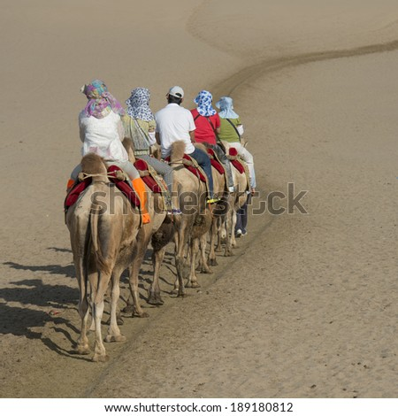 Tourists riding camels at Mingsha Shan, Dunhuang, Jiuquan, Gansu Province, China