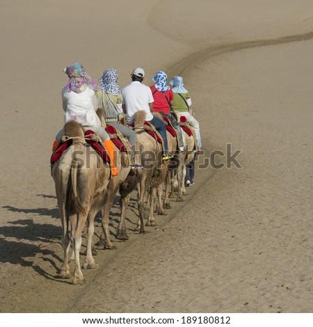 Tourists riding camels at Mingsha Shan, Dunhuang, Jiuquan, Gansu Province, China - stock photo