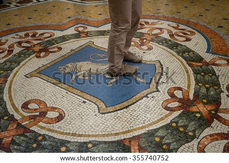 Tourists rotate around the bull's genitals in Galleria Vittorio Emanuele. A tradition to have good luck.   - stock photo