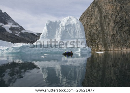 Tourists sailing next to an iceberg in the high arctic (Greenland) - stock photo