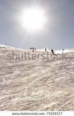 Tourists skiing in winter snow mountain landscape with blue sky. Sunshine. France Alps. - stock photo