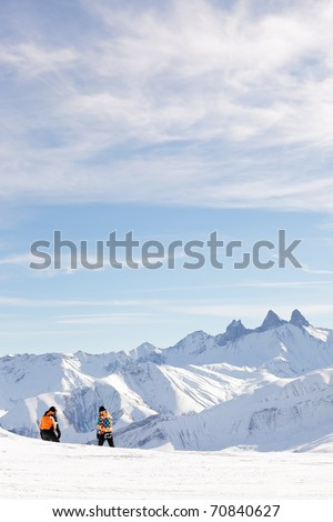 Tourists standing in winter snow mountain landscape with blue cloudy sky. Alps. France.