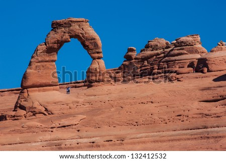 Tourists standing underneath Delicate Arch, Arches National Park, Utah - stock photo