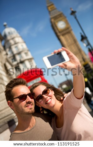 Tourists taking a picture in London with their phone