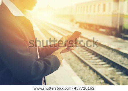 Tourists travelers ,business man consulting gps and guide from smart phone in a train station,Hand holding smartphone with subway map application,checking message sms e-mail or train schedule,vintage - stock photo