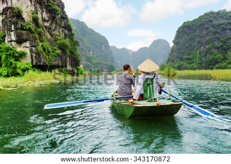Tourists traveling in small boat along the Ngo Dong River at the Tam Coc portion, Ninh Binh Province, Vietnam. Rower using her feet to propel oars. Landscape formed by karst towers and rice fields. - stock photo