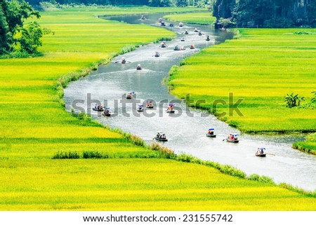 Tourists travelling on bamboo boats along a stream with paddy fields on both sides.  Location: Tam Coc Resort, Ninh Binh, Vietnam - a very famous sightseeing place. - stock photo