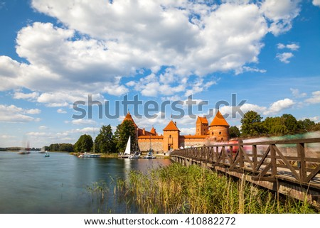 Tourists visit Trakai castle in sunny summer day, nice time to have boat trip. Long exposure, motion blur - stock photo