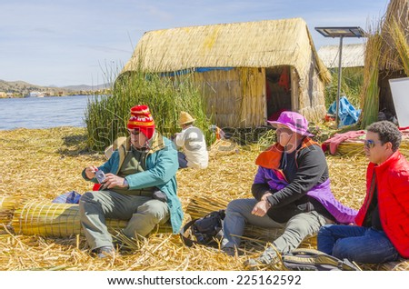 Tourists visiting one of Uros islands at Lake Titicaca, Peru - stock photo