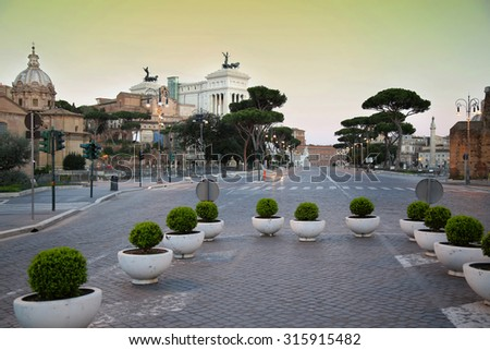 Tourists walk along Via dei Fori Imperiali in Rome, Italia ( photographed very early in the morning ) - stock photo