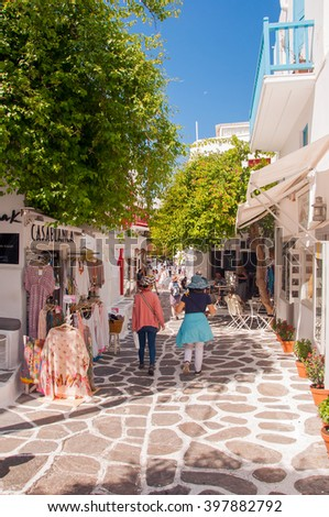 tourists walking around and shopping at shops in the narrow streets of Mykonos town, Mykonos island, Greece - stock photo
